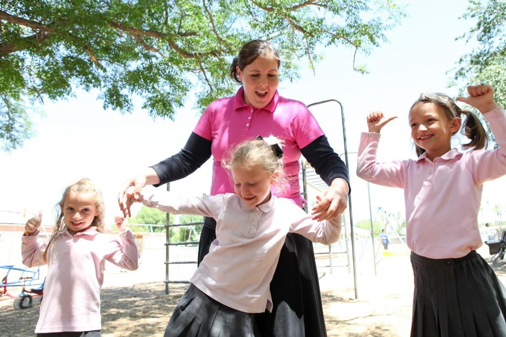 Ms. Jamie playing with the girls on the playground