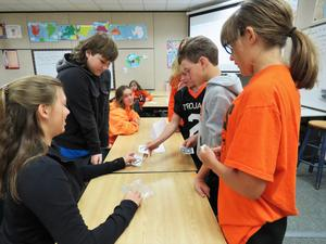 Students barter with groups to gain supplies they need.