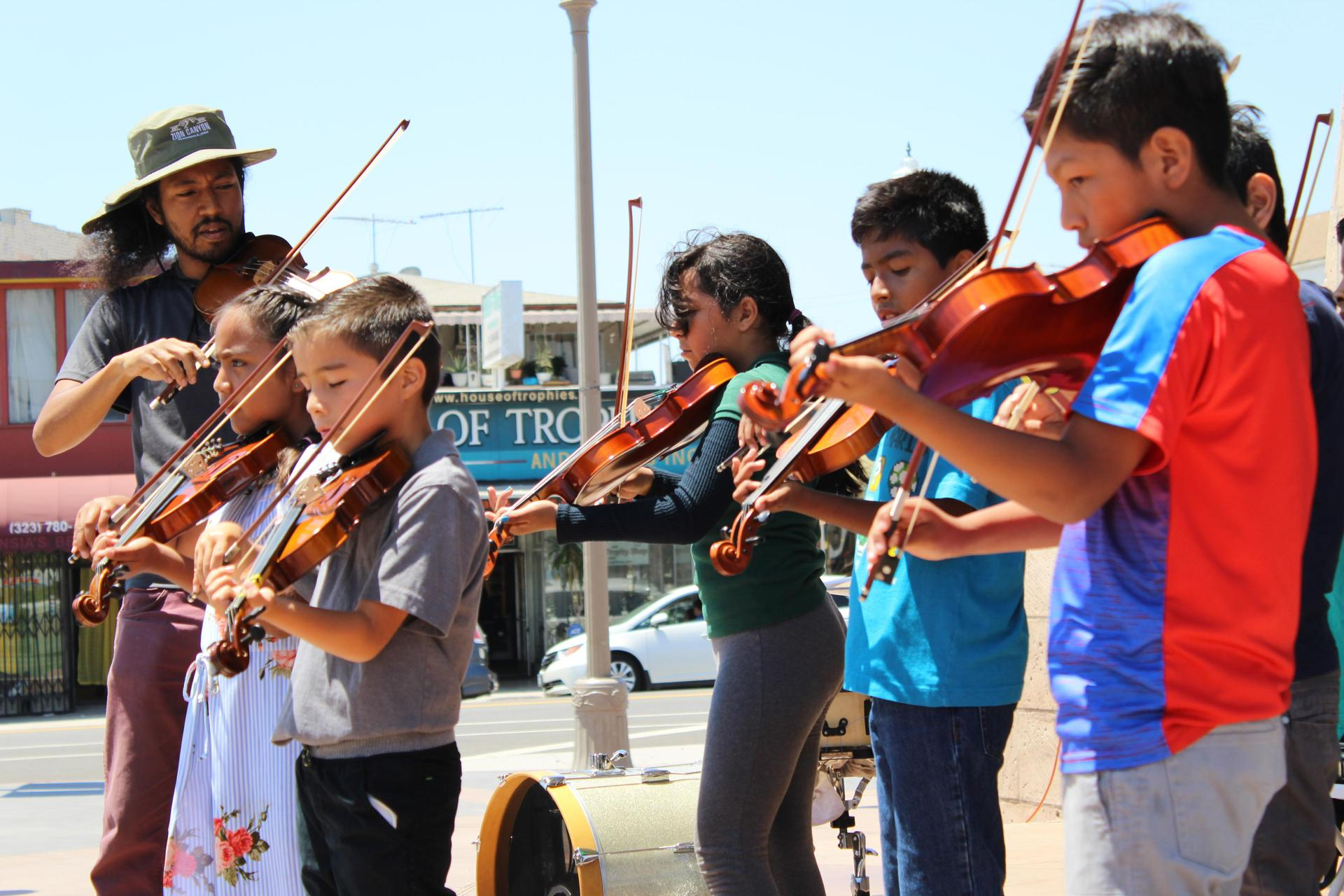 Students play violins at an outdoor festival