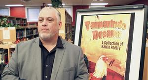 "Author Roberto Rocha stands in front of a poster of his book ""Tamarindo Dreams: A Collection of Barrio Poetry,"" while visiting with students at Edinburg High School."