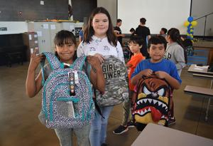 Roosevelt Elementary students show off their backpack selections during a backpack giveaway on Aug. 24. Cooper Moose Fitness in Pasadena donated 60 backpacks to Roosevelt students.