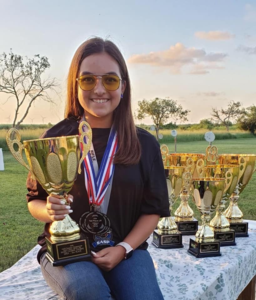 Issa Benavidez, a sophomore at McAllen High School, poses with her trophies. She took first place in Rifle Iron at the Scholastic Action Shooting Program National Championships in July.