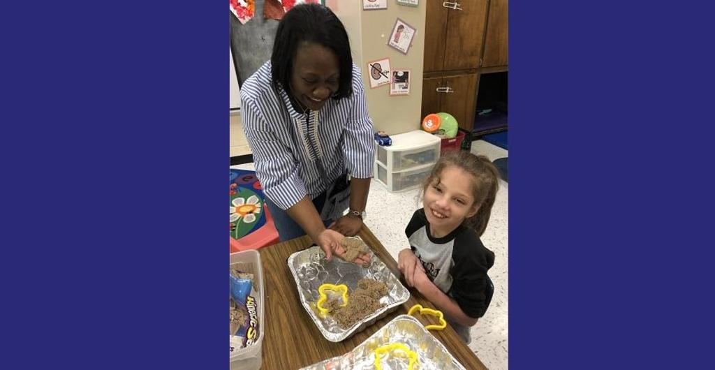 Principal working with young student in science