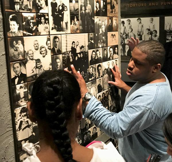 Student exploring photo wall of Holocaust victims