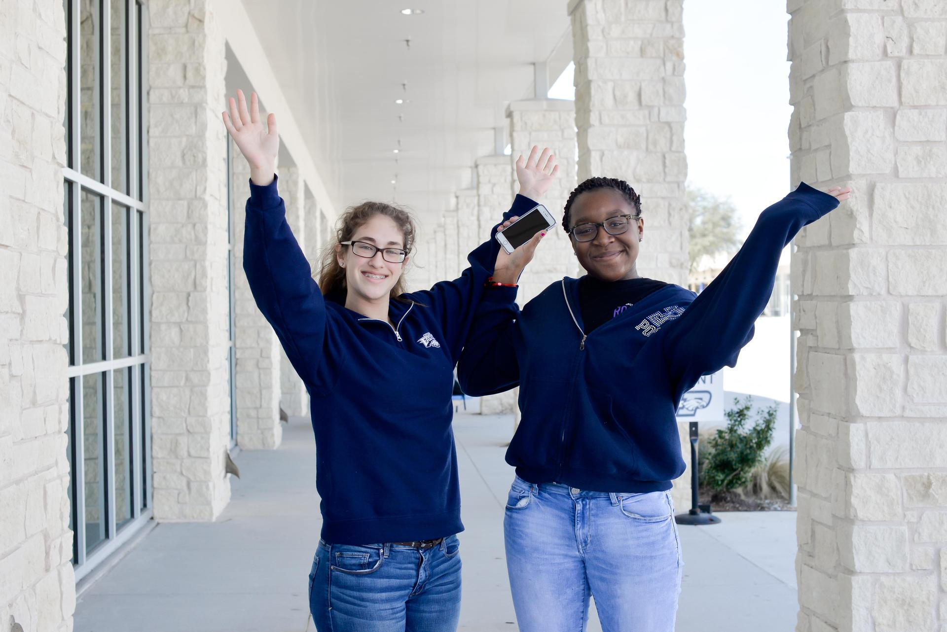 Two students waiving