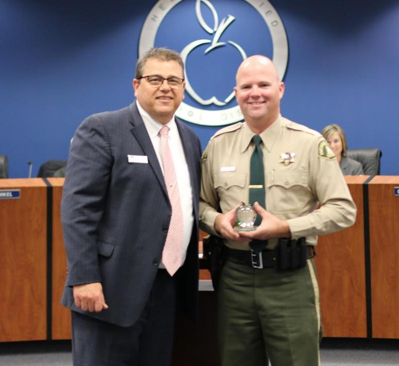 Picture of Deputy Jeremy Parsons receiving the Good Apple award from Darel Hansen