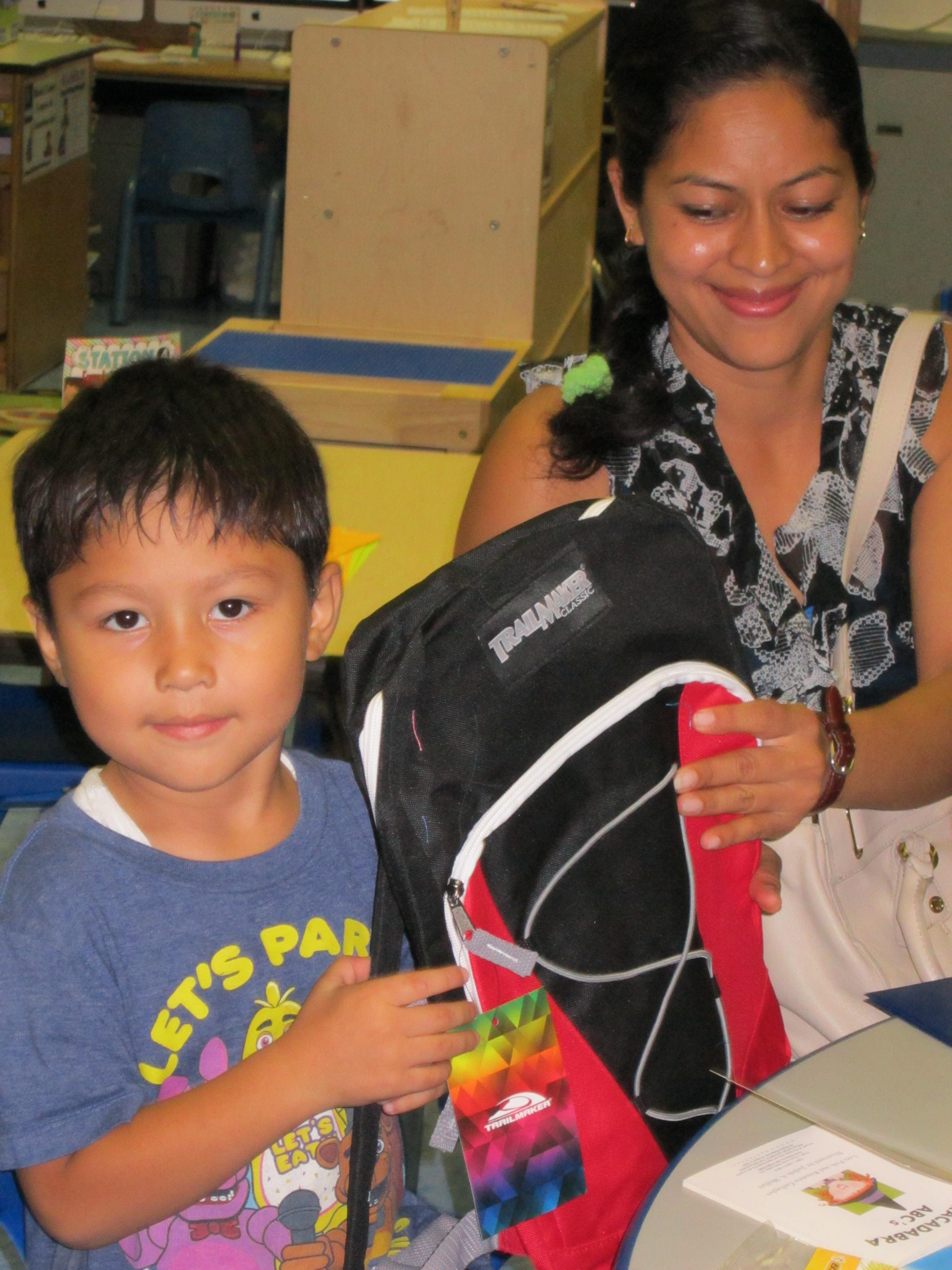parent and child holding to backpack gift