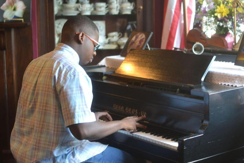 a photo of Baker High graduate Kenta Edwards playing a black baby grand piano at the Baker Heritage Museum
