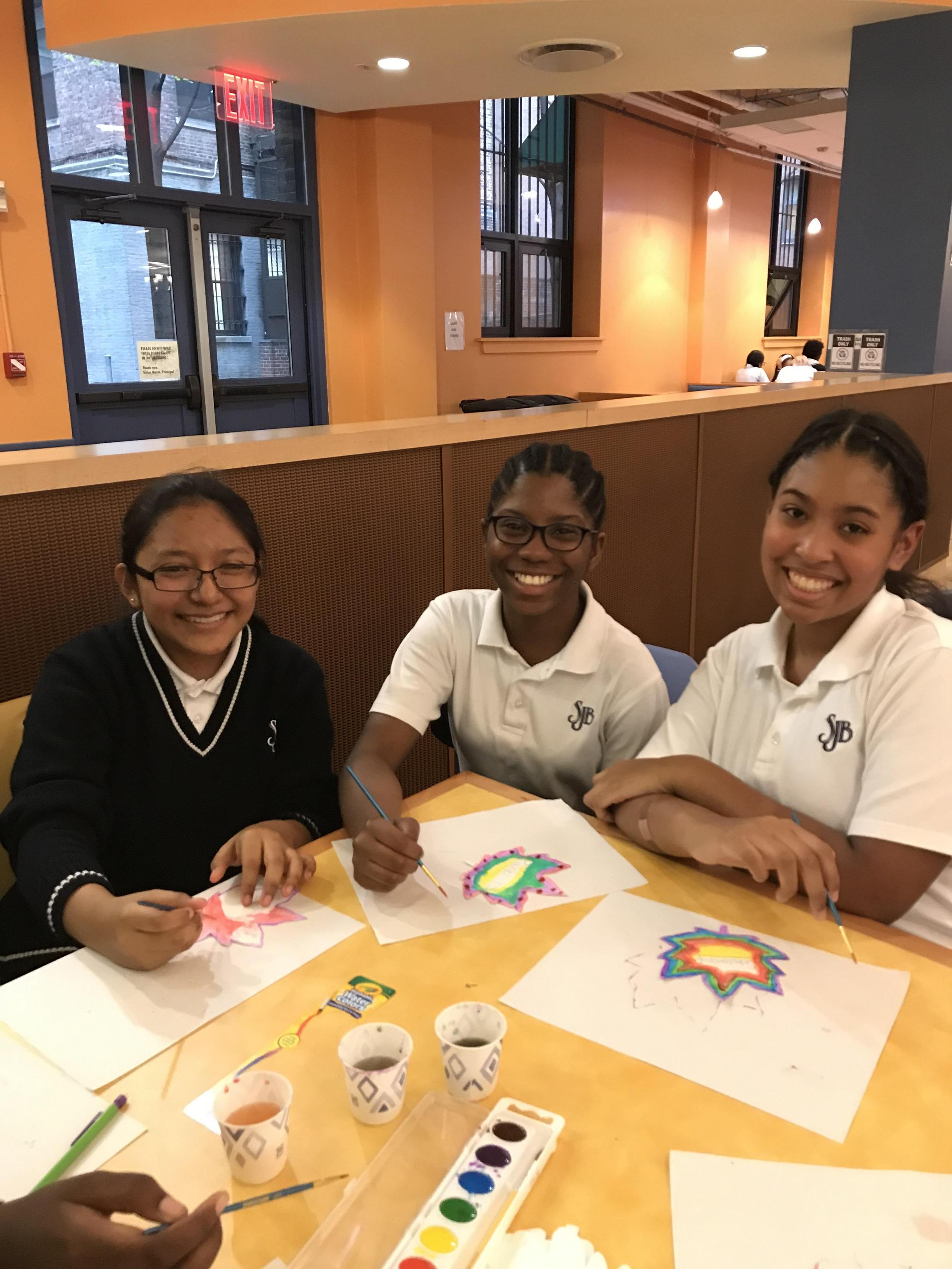Three girls sit at table with art supplies