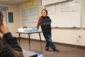 PACE High School guest speaker leaning on desk in front of class