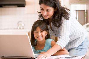Parent helping a child on a laptop