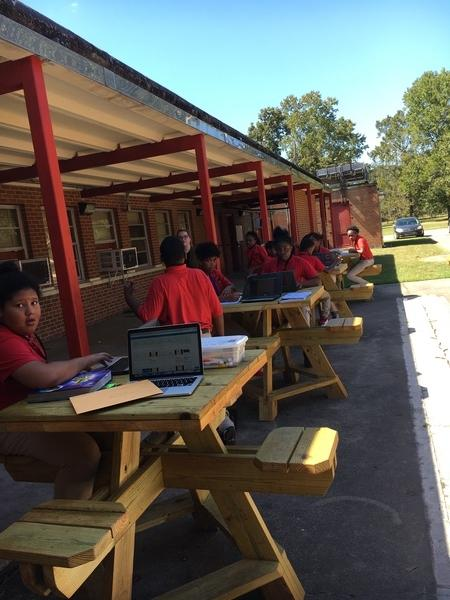 A photo of Baker Middle School Students learning outdoors in a natural environment
