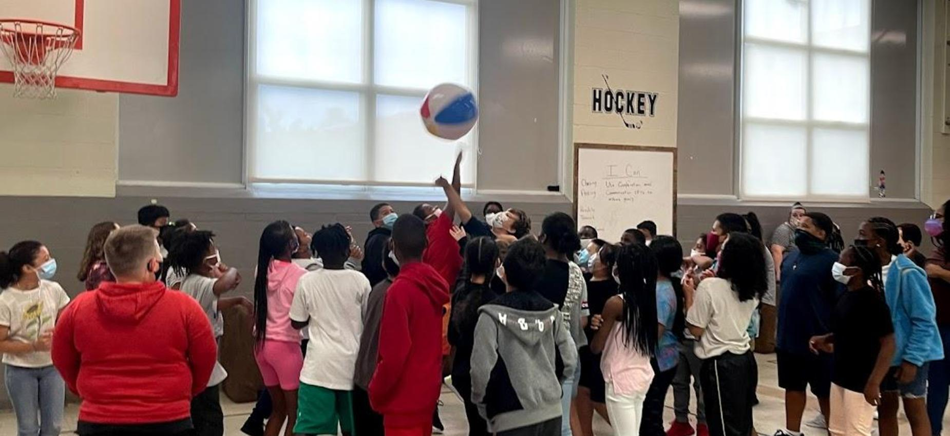 Students bouncing a beach ball during a family meeting.