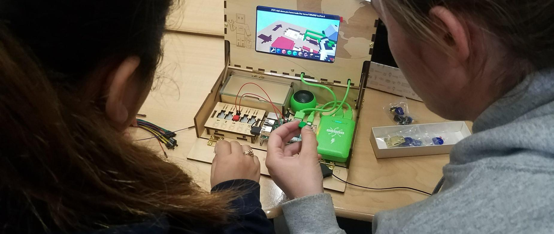 2 female students learning about programming and circuitry by building a computer