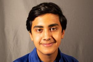 Headshot photo of Ali, wearing a royal blue shirt. He has dark brown hair and is grinning.