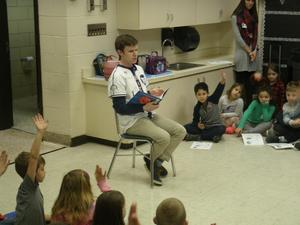 Hi-Toms representative reads to students.