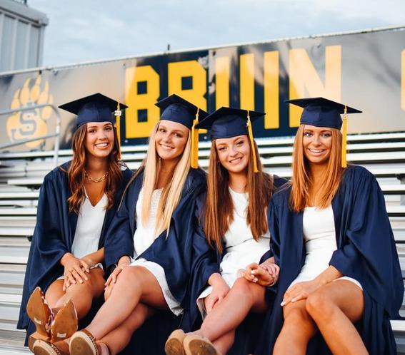 4 teen girls wearing graduation cap and gowns sitting on bleachers
