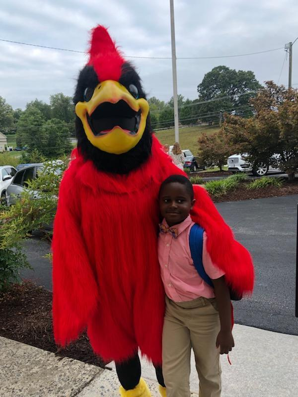 Cardinal mascot hugs student on opening day of school.