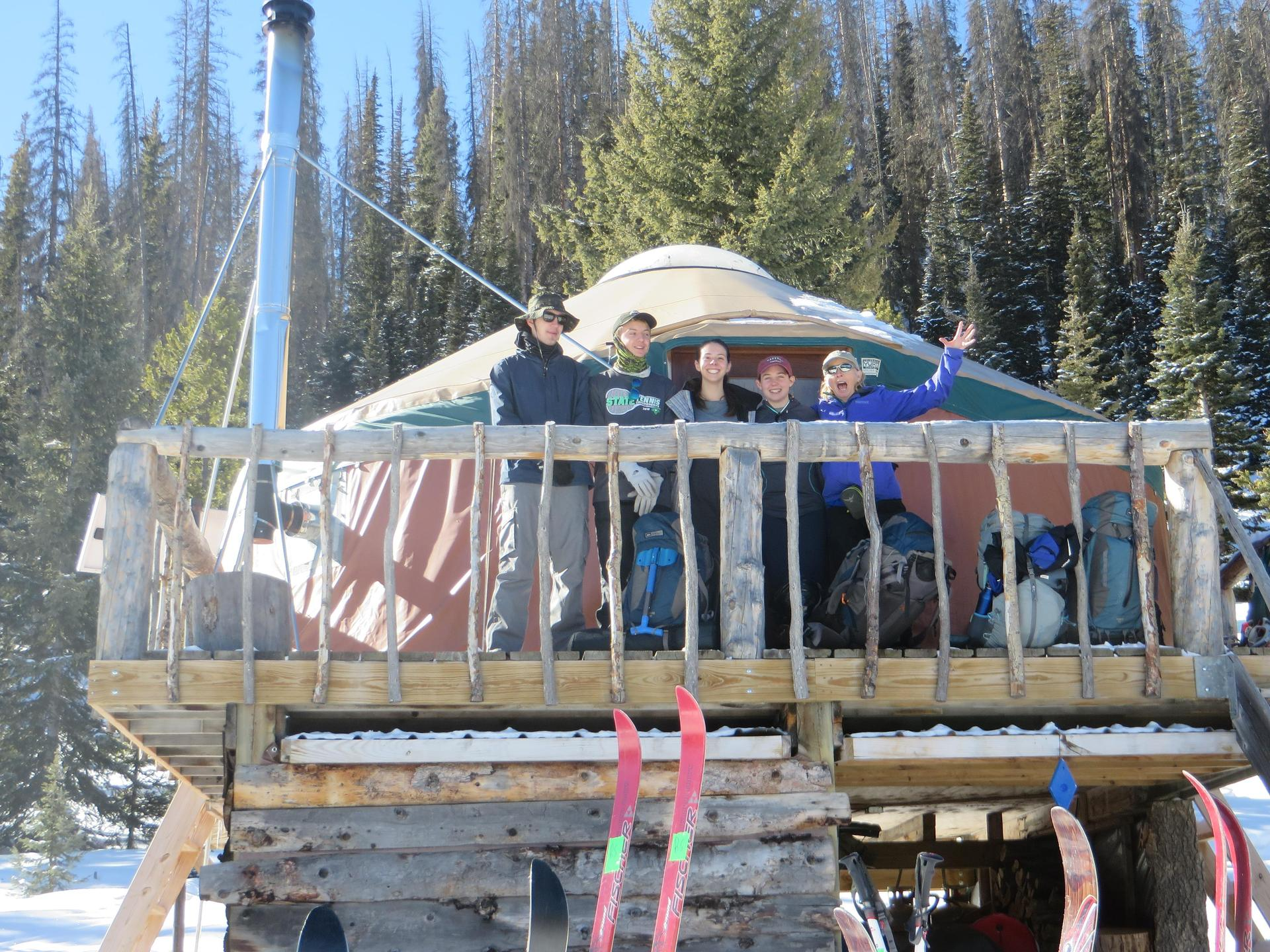 Students pose on deck outside of a yurt
