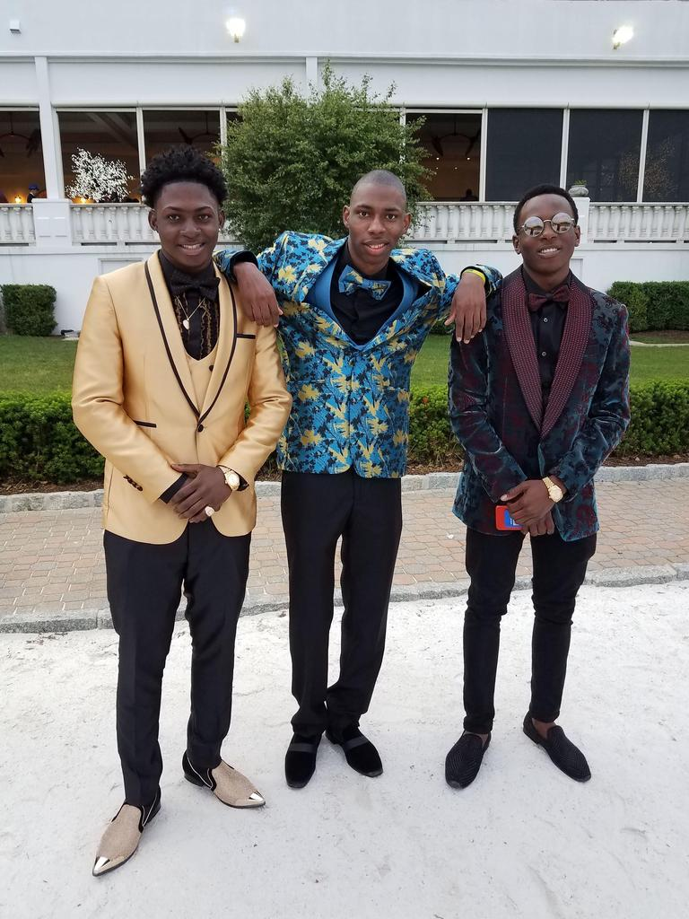 three suited students smiling