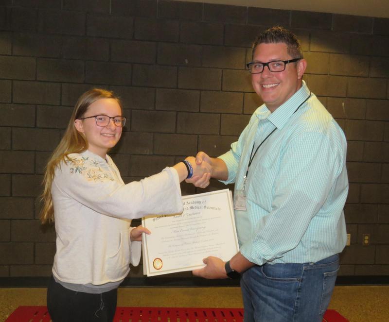Emma VanSprange accepts a certificate of honor from High School Principal Tony Petersen.