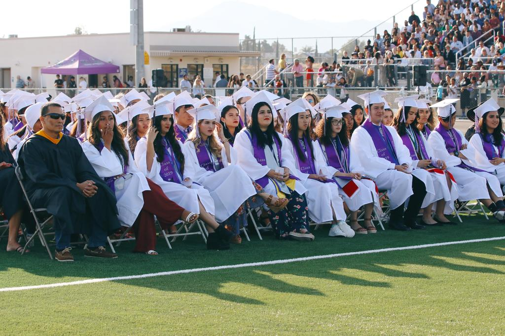 Vista Del Lago High School Class of 2019 grads sitting on field