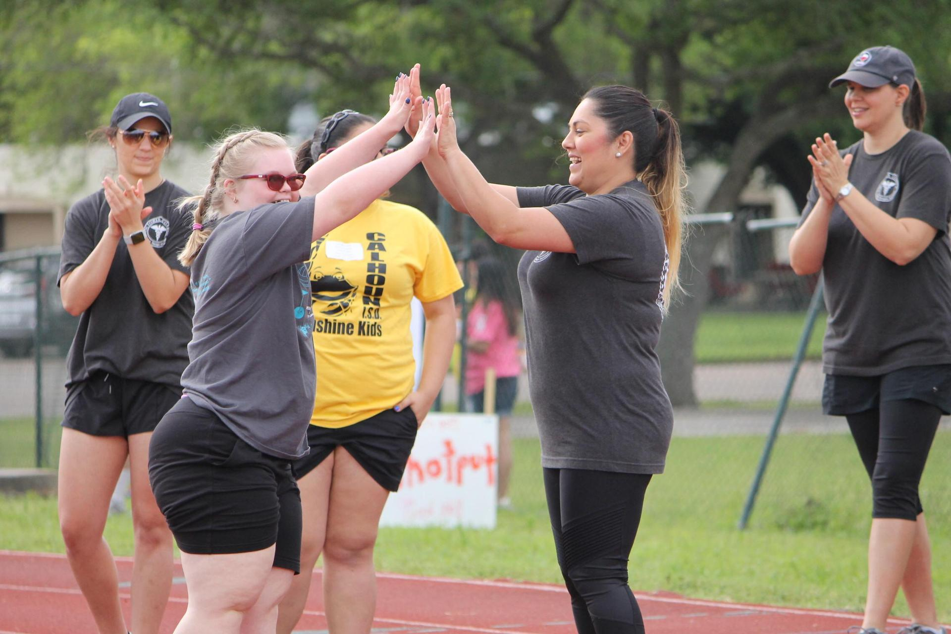 student high fiving a volunteer at the finish line of a race