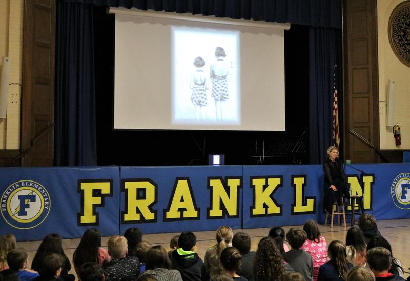 "Photo of:  Franklin 5th graders listen as actor Elizabeth Rainer performs ""Through the Eyes of a Friend"" on April 1, which is told from the viewpoint of a fictional ""best friend"" of Anne Frank and uses archival film and sound."