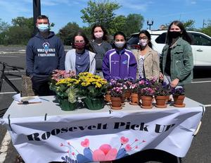 Photo of members of the Roosevelt Student Council in front of table of flowering plants as part of a spring fundraiser