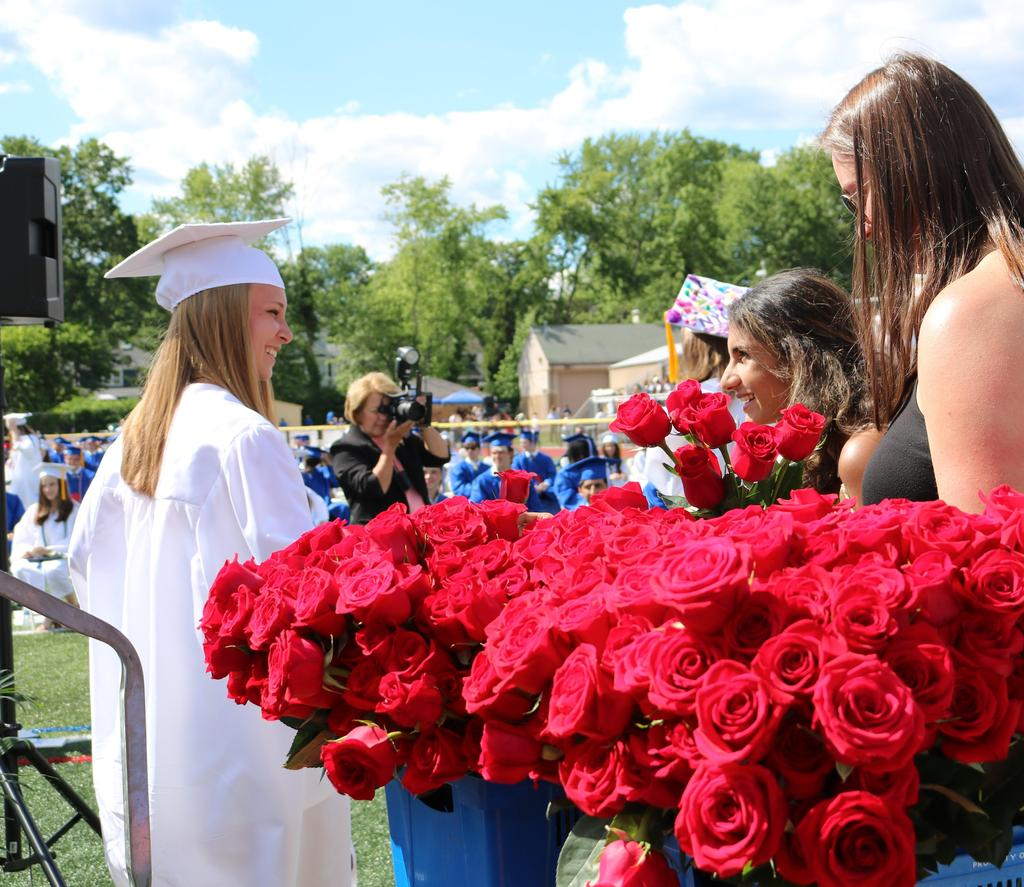 :  A Westfield High School graduate of the Class of 2021 accepts a rose and congratulations upon receiving her diploma
