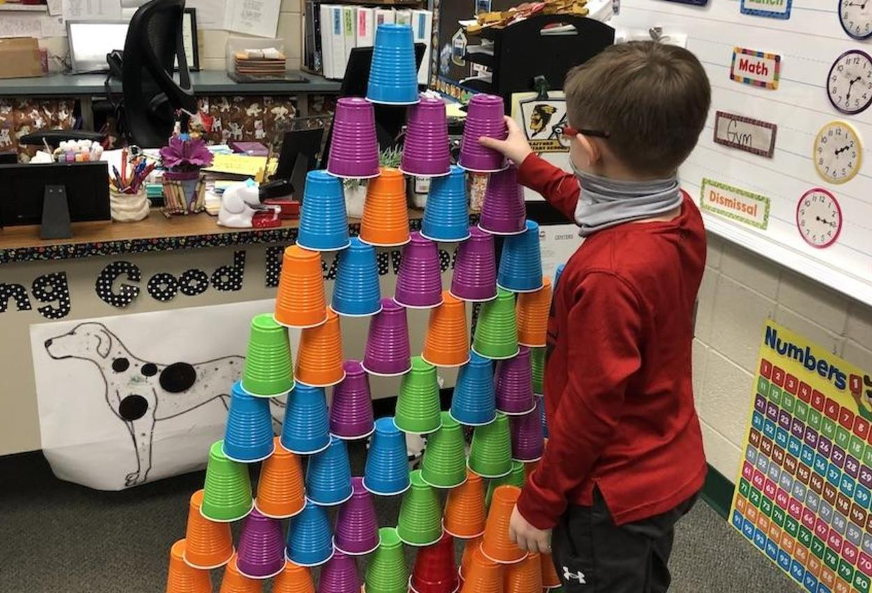 student building pyramid of cups