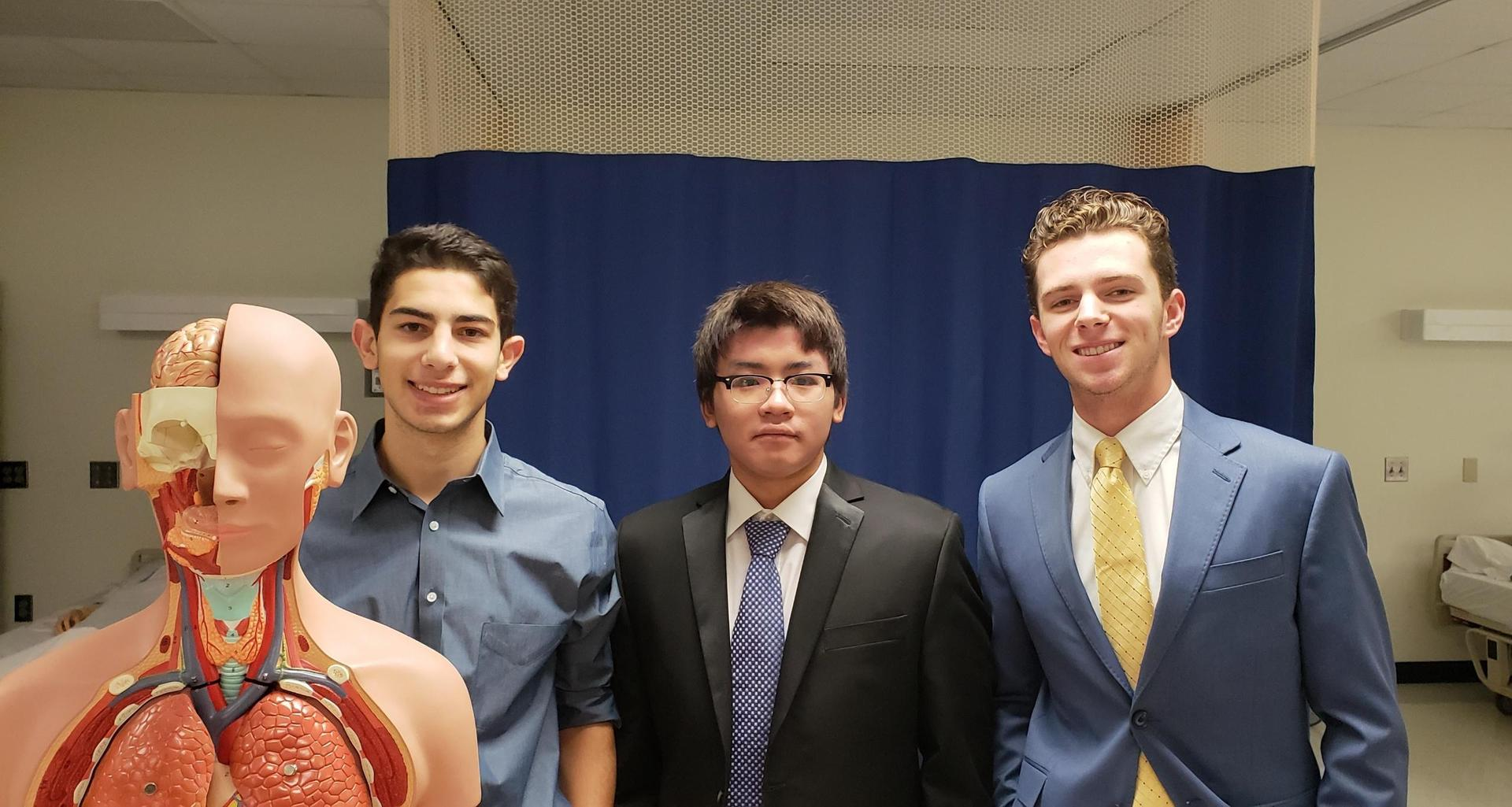 three health science boys with mannequin