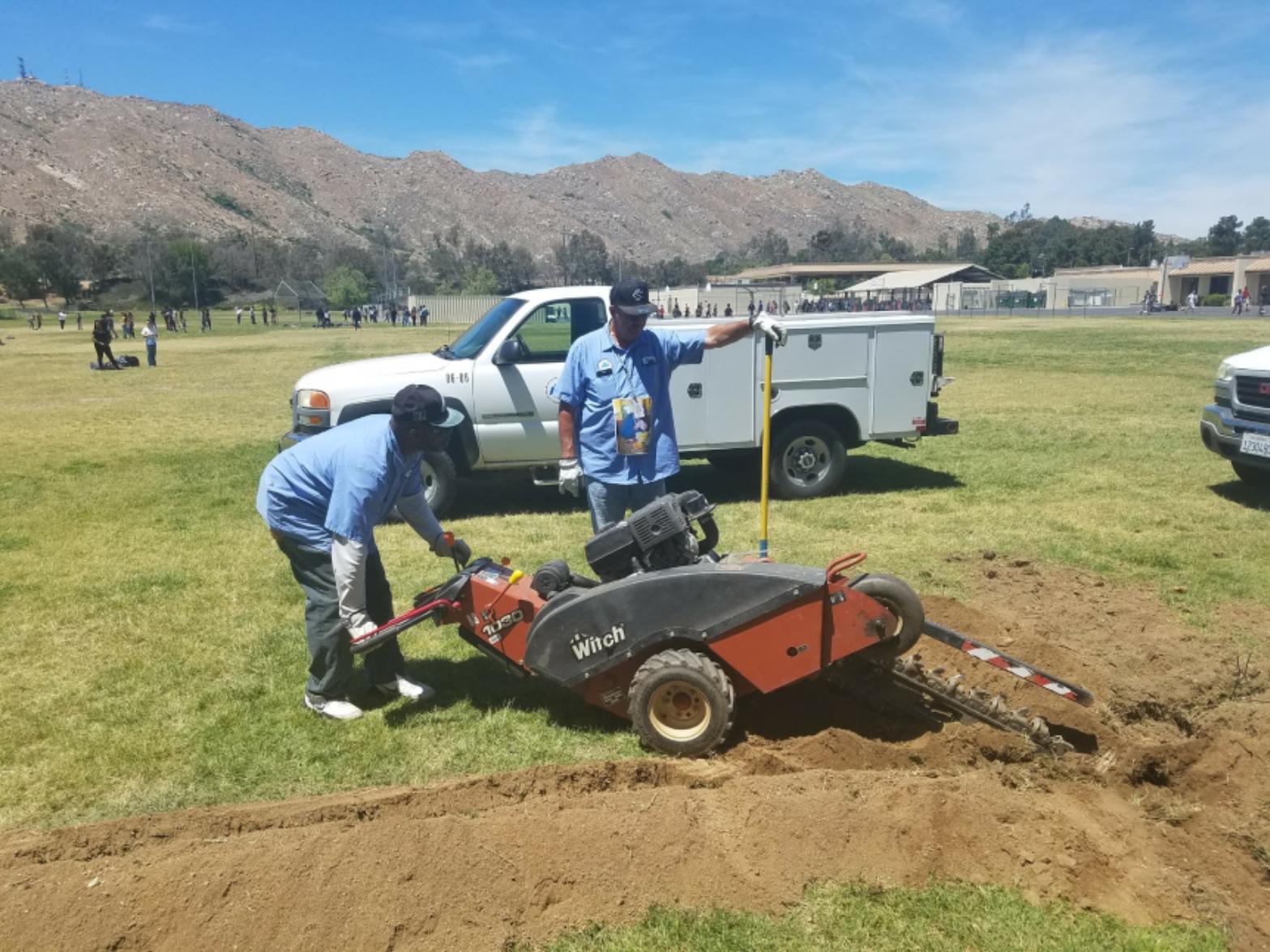 2 men working with trenching machine