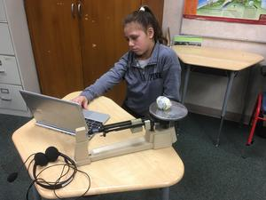 student with computer and triple beam balance on her desk