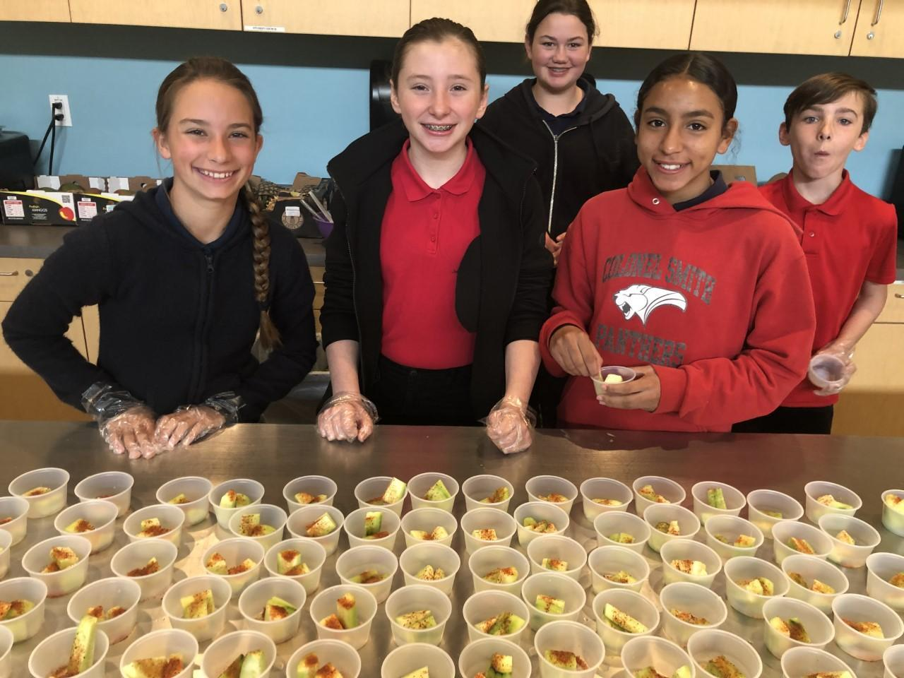 Students hand out healthy food samples.