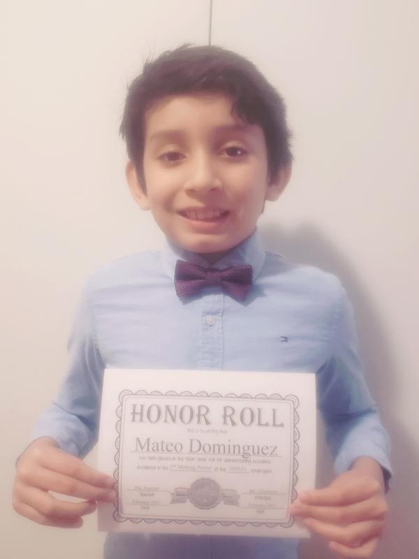 Mateo holding honor roll certificate