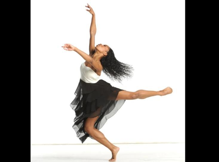 woman dancing in a black skirt and white top