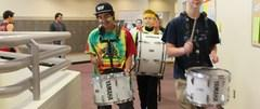 Photo of students marching with drums in the hall