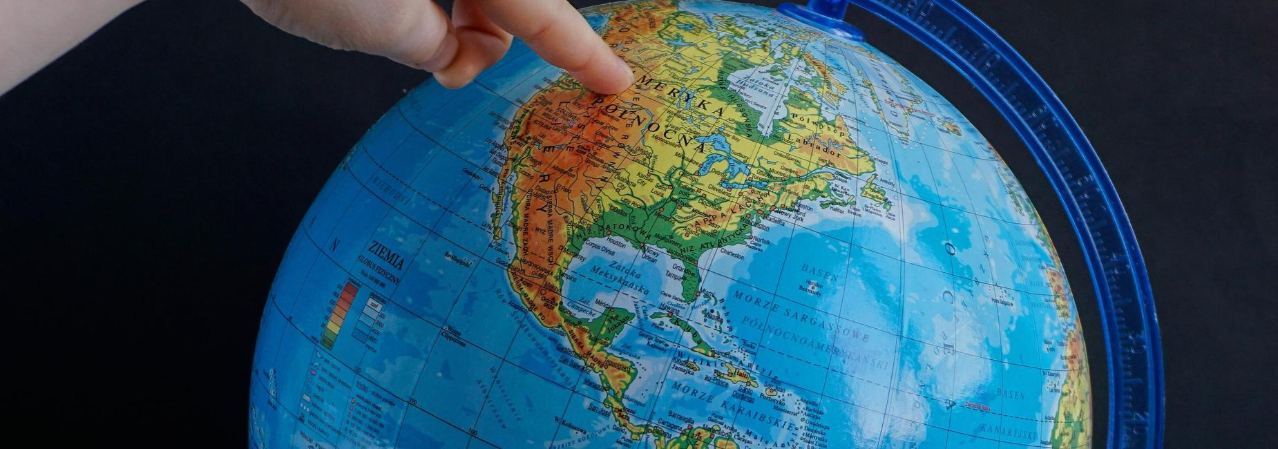 This is a picture of a globe with a finger pointing to America.  The places on the globe was written in another language.  The knowledge that we gain in school can carry us all over the world.