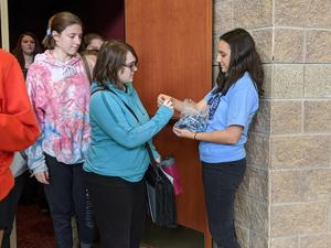 A SADD member hands out a bracelet