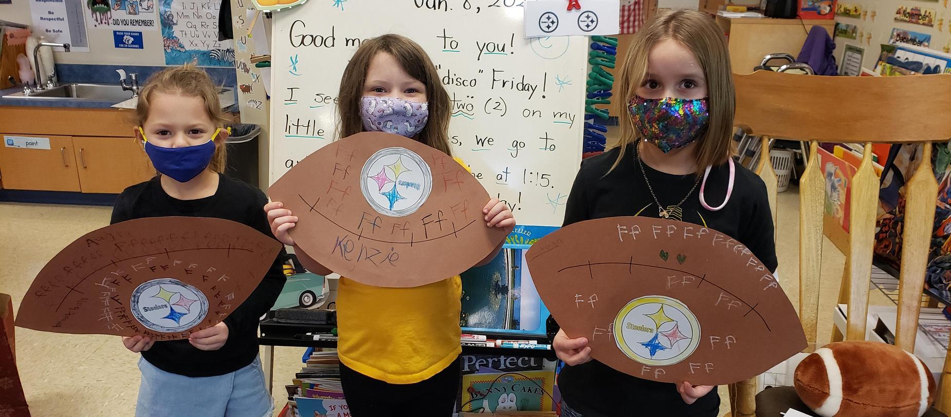 kindergarten students posing with footballs