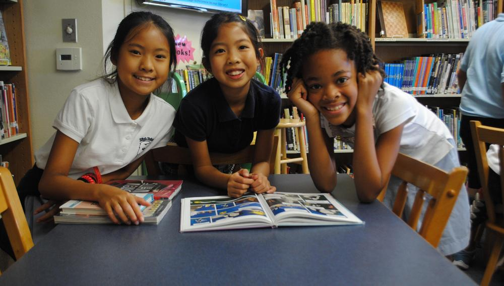 Three smiling girls in library.