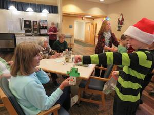 Students give homemade holiday ornaments to residents at Carveth.