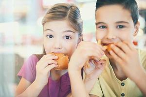 A boy and girl eating lunch