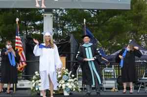 Graduate in white gown poses and waves after receiving her diploma