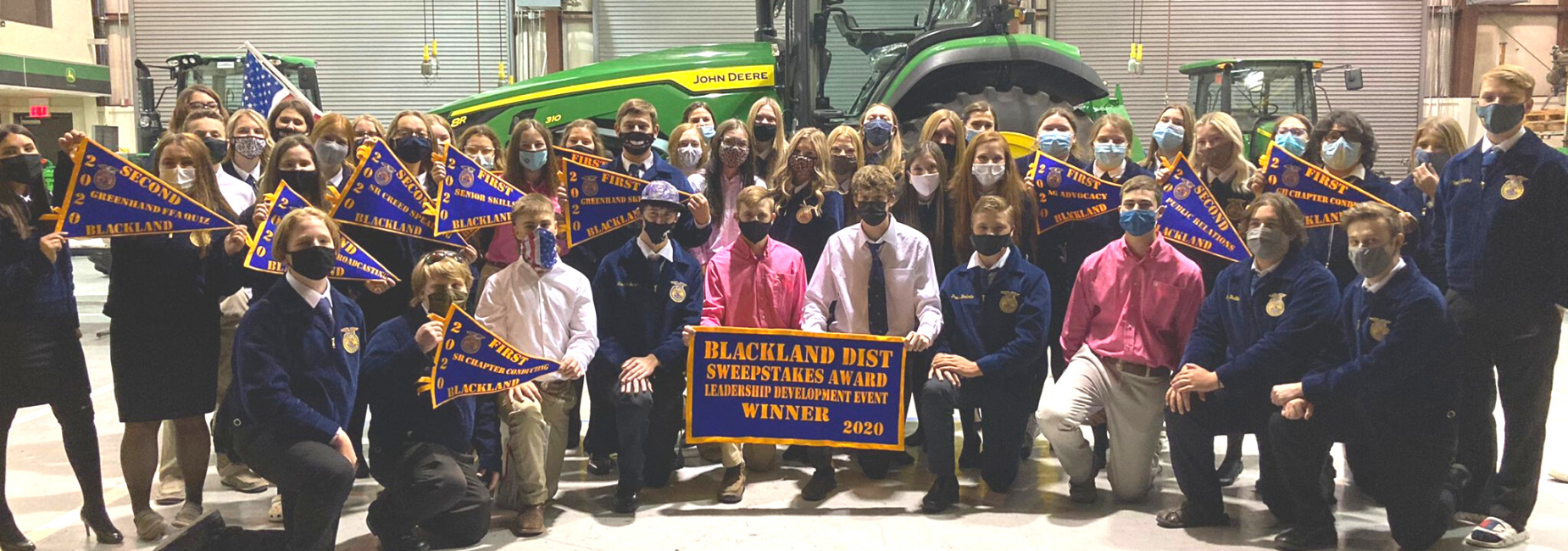 large group of students wearing FFA jackets holding award pennants