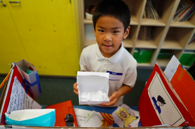 student holds up project (box he made)