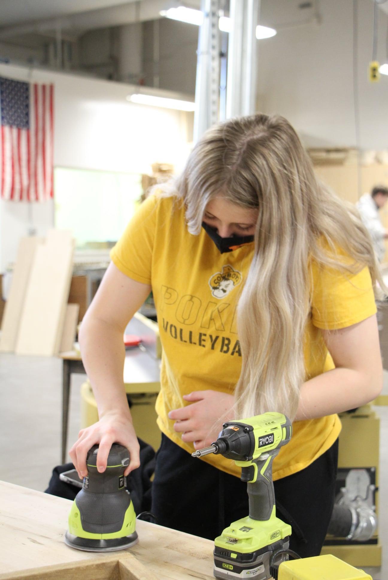 Girl sanding in wood shop class