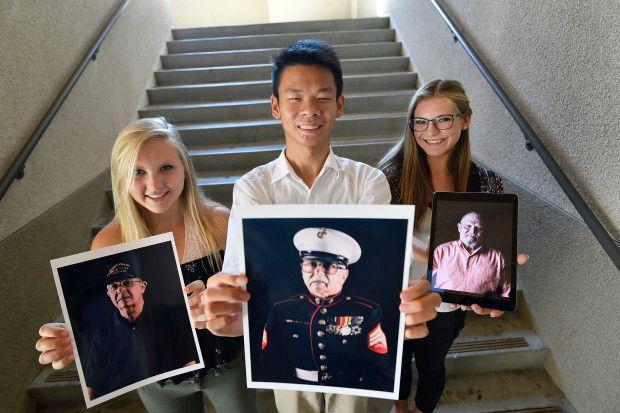 Three students posing with photos of Vietnam Veterans