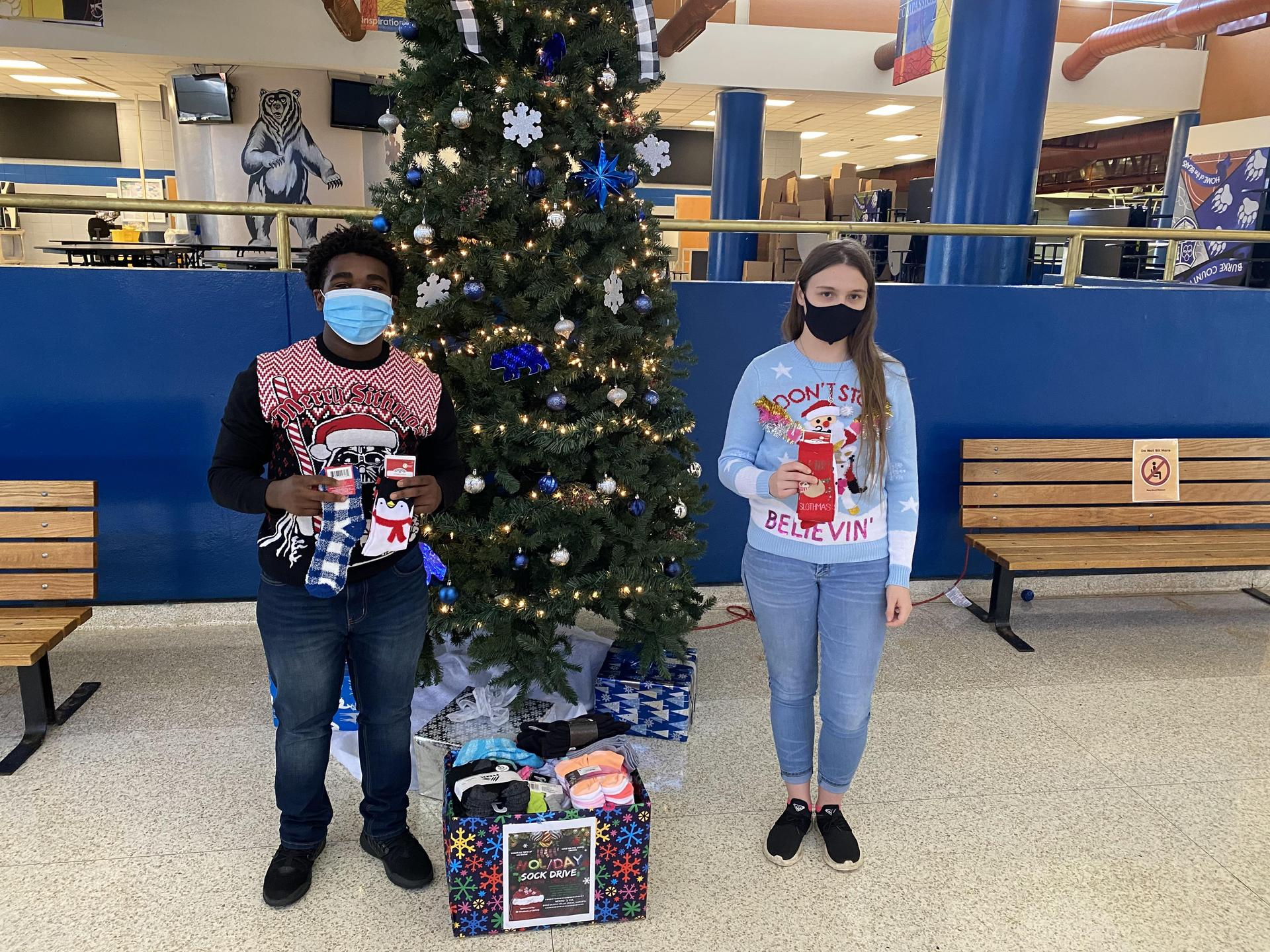 2 IB students standing by a Christmas tree holding socks.